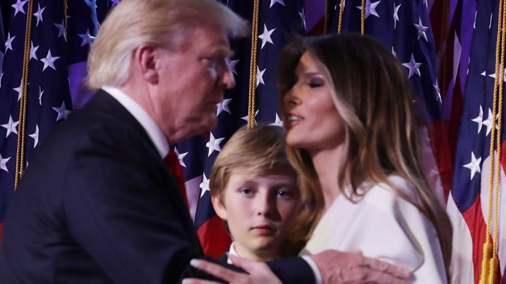 Republican president-elect Donald Trump embraces his wife Melania Trump, as their son Barron looks on