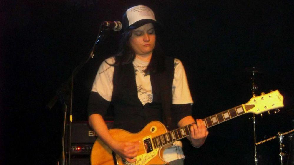 Anna Dragicevic playing a guitar
