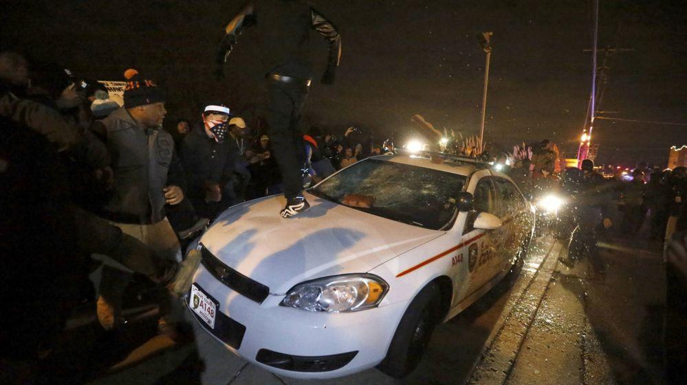 Protestors damaging a police car