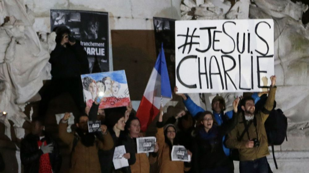 "People holding a placard with ""#JeSuisCharlie"" written on it"