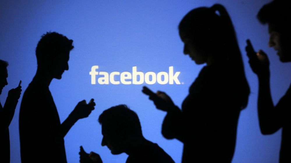 People are silhouetted as they pose with mobile devices in front of a screen projected with a Facebook logo