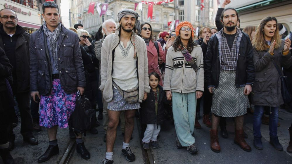 Men in a street march wearing skirts