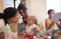 Zaneta (centre) and her younger sister Martina (left) entertain baby Roman – Zaneta's grandson