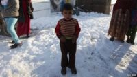 A Syrian child stands in the snow in a refugee camp in the Beqaa Valley, Lebanon. Photo: 12 December 2013