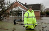 5. A Moorland villager clears debris in his front garden