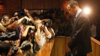 Photographers take photos of Olympic athlete Oscar Pistorius as he stands in the dock during his bail hearing at the magistrates court in Pretoria, South Africa, Friday, 22 February 2013
