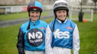 "Jockey Carol Batley, representing the ""No"" vote, (L) and jockey Rachael Grant, representing the ""Yes"" vote, prepare to take part in a ""Referendum Race"" sponsored by Ladbrokes at Musselburgh racecourse on September 15, 2014"