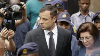 Oscar Pistorius (centre) accompanied by police officers as he leaves the high court in Pretoria