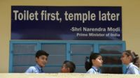In this September 22, 2014, photo schoolchildren talk in front of a poster bearing a quote from PM Narendra Modi in Delhi.