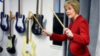 First Minister of Scotland Nicola Sturgeon, holds up drum sticks during a visit to The Kabin community learning centre