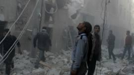 Hombre miran edificios destruidos por bombas de barril