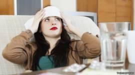 Mujer con compresa fría en la frente