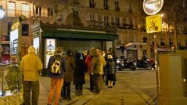 Fila em frente a uma banca de jornais em Paris