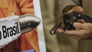 Un hombre sostiene un revólver junto a un cartel en el primer día de una campaña de desarme en Brasil.