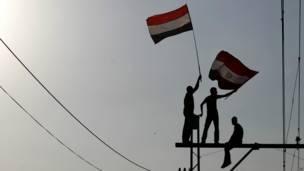 Manifestantes con banderas arriba de los postes, AFP