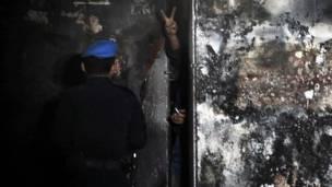 Seorang napi mengacungkan tanda perdamaian di balik pagar penjara, AFP