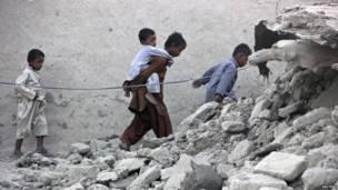 Supervivientes del terremoto caminan sobre los escombros de una casa de barro, después de que la vivienda se derrumbara tras el temblor en la ciudad de Awaran.
