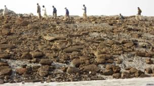 Personas caminan sobre la isla que emergió del  tras el sismo frente a las costas del puerto de Gwadr.