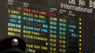 Cảnh sát Trung Quốc đứng ở dưới một bảng báo thông tin hàng không.