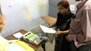 दिल्ली के एक मदान केंद्र पर मतदान की तैयारी में लगे चुनाव अधिकारी