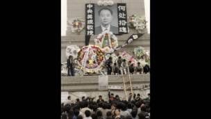 Estudiantes depositan coronas frente a un retrato de Hu Yaobang. 19 de abril, 1989. AFP