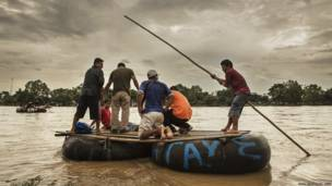 Migrantes cruzando río
