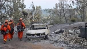 """Bomberos caminan a un lado de un carro destruido por el incendio forestal conocido como """"El incendio de arena"""" ("""