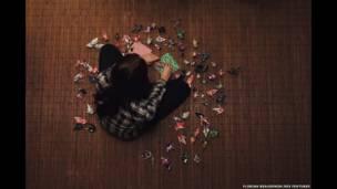 Foto de una persona con figuras de origami, por Florian Beaudenon