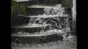 El agua de lluvia circula a través de Mawsynram durante un fuerte aguacero. Amos Chapple / Rex Features