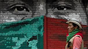 Un guardia indígena pasa frente a un mural en Toribío