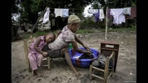 Jestina Koko lava ropa mientras su hija la observa. Fotografía: Renée C. Byer.