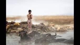 Un muchacho de un pueblito congelado está parado al ladode una piscina natural de aguas termales, una foto