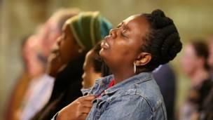una mujer entona el himno de Sudáfrica