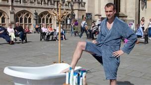 Chris van Tulleken con tina y bata en una plaza inglesa