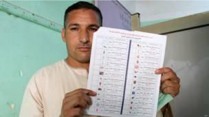 ناخب يحمل استمارة التصويت