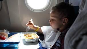 Un niño comiendo en un avión