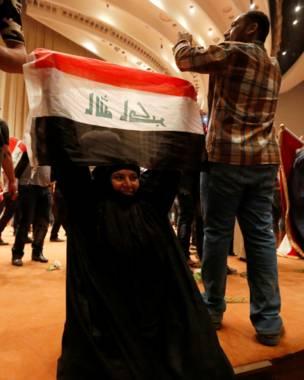 Mujer con una bandera de Irak en el congreso
