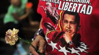 Un seguidor sostiene una imagen de Hugo Chávez
