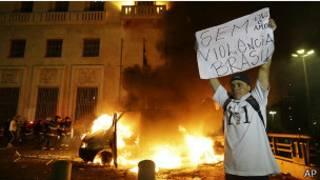 Manifestante ergue cartaz diante de veículo incendiado em frente à Prefeitura de São Paulo