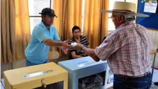 Hombre con sombrero de huaso votando
