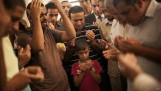 Egípcios em funeral de homem morto em confrontos no sábado, no Cairo (AP)
