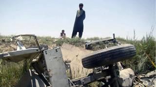 Un hombre mira los restos de un vehículo tras un ataque bomba.