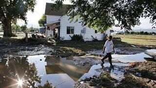 mujer pasa frente a su casa inundada en el centro de Colorado