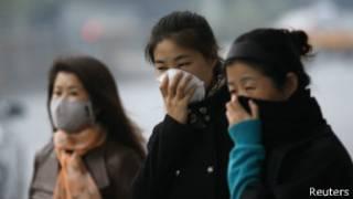 Mujeres visten máscaras contra la polución en Pekín