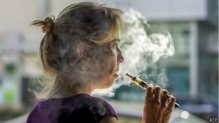 Mujer fuma cigarrillo electrónico
