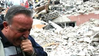 Un hombre frente a una montaña de escombros tra un terromoto en Turquía en 2011
