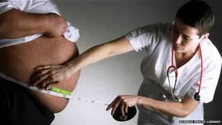 Una enfermera mide la barriga de hombre obeso
