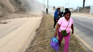 Una mujer camina por la Carretera Panamericana tras el sismo