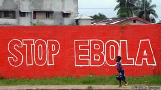 Niña pasea frente a un graffiti contra el ébola