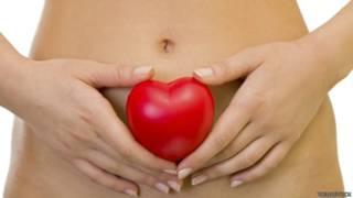 Una mujer que sostiene una forma de corazón sobre su vientre